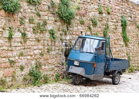 Visso, Italy - May 31, 2014: A Picturesque Old Alley With Dwellings And An Ancient Italian Vehicle A