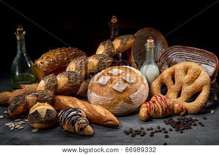 Composition Of Breads, Croissants And Rolls With Milk, Oil And Coffee Beans On Wooden And Black Back
