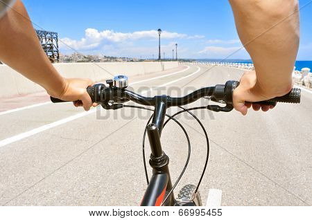 closeup of a young man riding a bike on a no traffic road