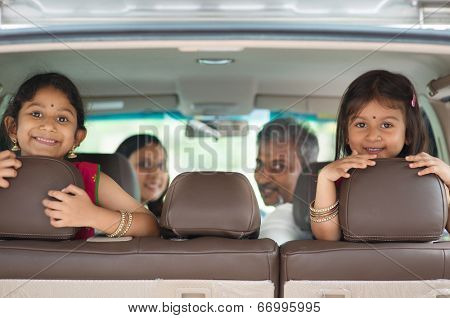 Happy Indian family sitting in car smiling, ready to vacation.  Asian parents and children.