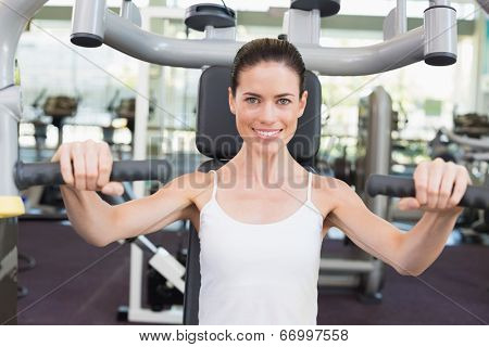 Fit brunette smiling at camera using weights machine for arms at the gym