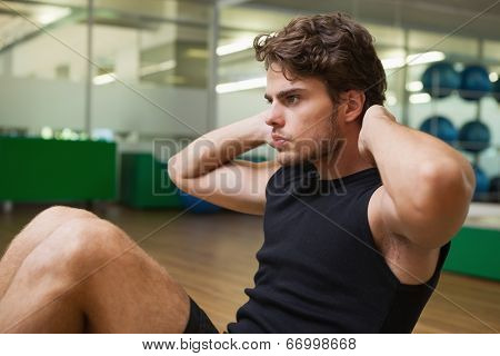 Fit handsome man doing sit ups in fitness studio at the gym