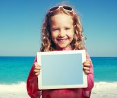 picture of children beach  - Child on the beach with tablet computer - JPG