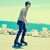 foto of roller-skating  - a young man roller skating near the sea - JPG