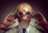 picture of gas mask  - Man wearing vintage gas mask and headphones listening to music - JPG