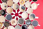 picture of flavor  - Coffee mecca with multiple assorted types and flavors of coffee in identical white mugs artistically arranged with converging handles in the centre on a red background overhead view - JPG