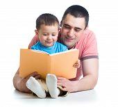stock photo of nurture  - dad reading a book to kid boy - JPG