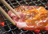 picture of chopsticks  - Grill pork on hot charcoal using chopstick - JPG