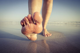 stock photo of barefoot  - Close up of feet walking barefoot along a beautiful beach on a sunny day enjoying the exercise - JPG