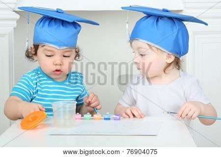 Young children in blue graduation hats paint colors at table