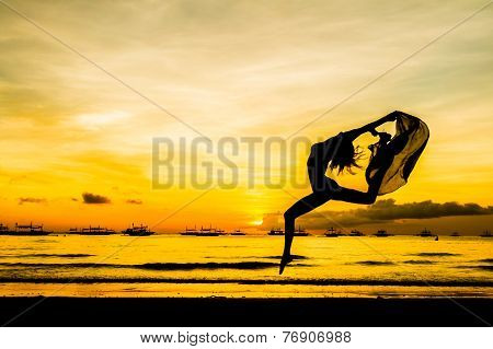silhouette of jumping girl on tropical sunset sea and sky background