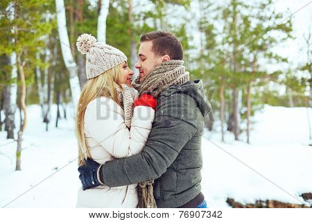 Young couple embracing in winter park