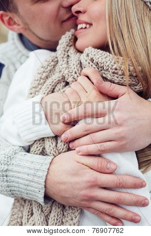 Young couple in sweaters embracing and kissing outdoors