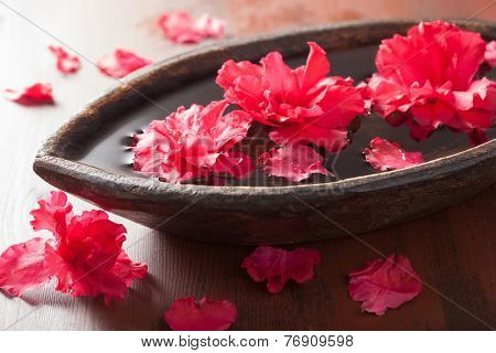 beautiful red azalea flowers in wooden bowl for spa