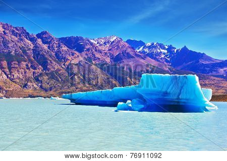 Ices and sun of Patagonia. White-blue huge icebergs float near a ship board. Excursion by tourist motor ship on Vyedm's lake