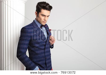 Handsome young fashion man posing near a white column while looking down and fixing his jacket.