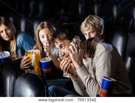 Angry family looking at man communicating on mobilephone in cinema theater