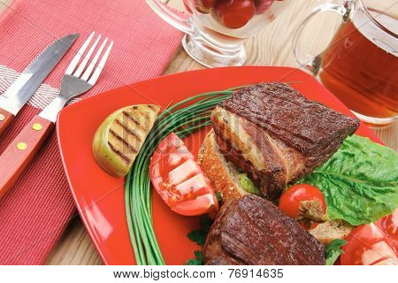 meat savory : beef fillet mignon grilled and garnished with vegetables , juice and olives on red plate over wooden table