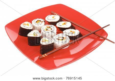 Japanese Cuisine : Sushi Maki Roll with Vegetables and Salmon inside . on red dish with sticks isolated over white background