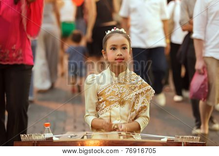 CHIANG MAI, THAILAND, FEBRUARY 26, 2012: A little girl dressed in traditional clothes is playing dulcimer instrument in the street during the week-end night market in Chiang Mai, Thailand