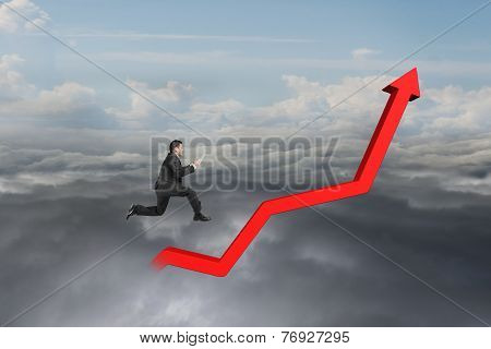 Businessman Holding Tablet And Jumping On Red Growth Trend Line