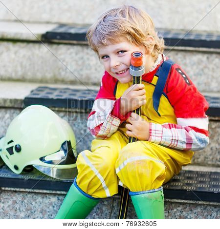 Funny Little Child Of Four Years Having Fun As Fireman, In Uniform And Helmet.