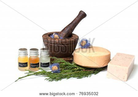 Wooden pounder with bottles of organic oils and soap isolated