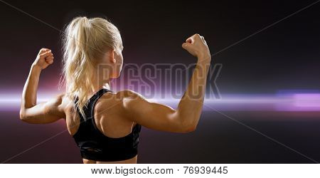 fitness, sport and diet concept - sporty woman form the back flexing her biceps
