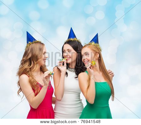 holidays, people and celebration concept - smiling women in party caps blowing to whistles over blue lights background