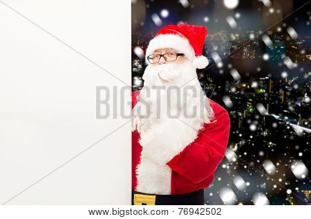 christmas, holidays, advertisement and people concept - man in costume of santa claus with white blank billboard making hust gesture over snowy night city background