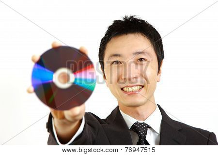 Japanese businessman showing a media disc