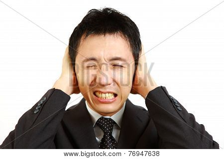 Japanese businessman holding hands on his ears, protecting himself from noise