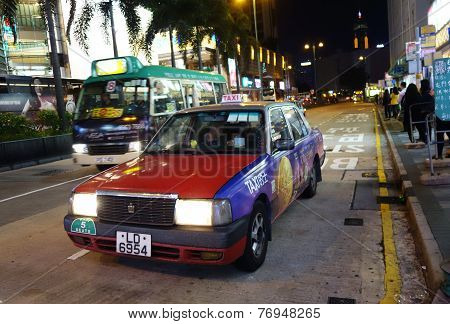 A Taxi Travels On The Road In Hong Kong
