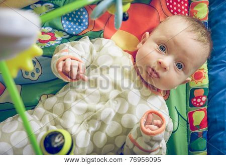 Baby With Blue Eyes Playing With Toys