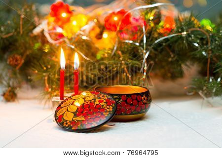 Christmas arrangement with candles and boxes in Khokhloma painting.