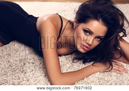 Sexy Girl With Dark Hair In Lace Black Dress Lying On Beige Carpet
