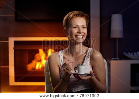 Happy woman laughing, drinking coffee in cosy room by fireplace.