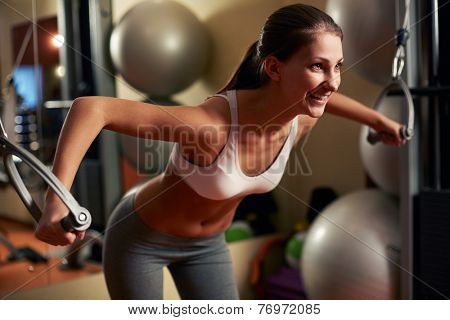 Young woman lifting weights at home gym