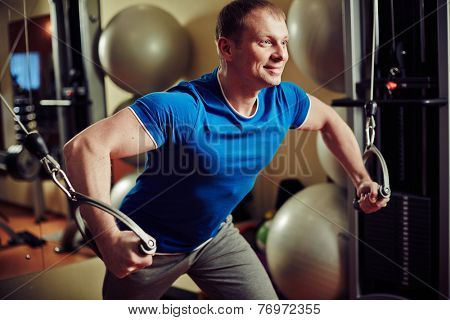 Man training lifting weights at exercise machine