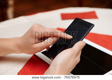 Woman with mobile phone and tablet computer in cafe shop