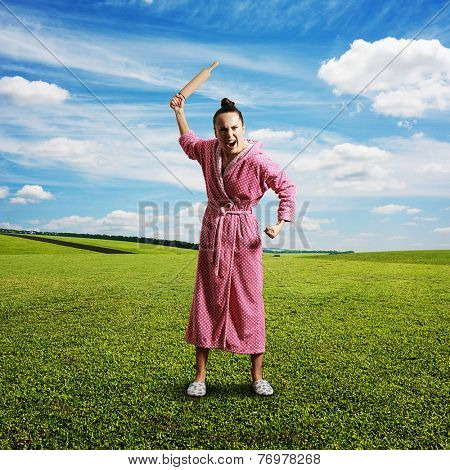 discontented screaming housewife holding rolling pin and looking at camera. photo at outdoor