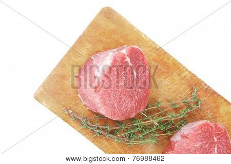 fresh red meat : two raw beef fillet chops on wooden board with small thyme twig ready to prepare . isolated over white background