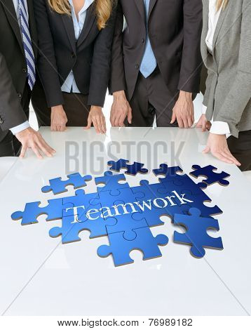 Meeting with people around a table with a puzzle with the word teamwork
