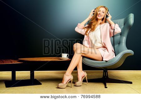 Beautiful smiling girl enjoying listening to music in headphones. Interior, furniture. Leisure.