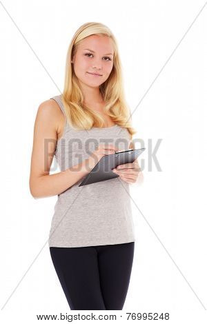 Attractive woman in sports wear holding clipboard. All on white background.