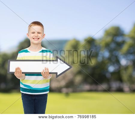 advertising, direction, nature and childhood concept - smiling little boy with white blank arrow pointing right over park background