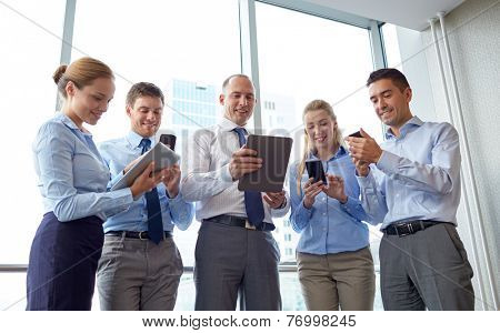 business, teamwork, people and technology concept - business team with tablet pc and smartphones meeting in office