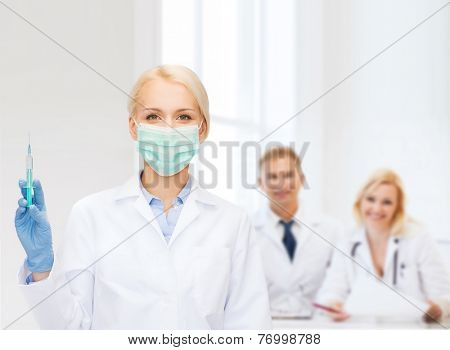 healthcare and medicine concept - female doctor in mask holding syringe with injection