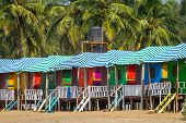 picture of beach hut  - Colorful huts on the sandy beach with palm trees background in Goa - JPG