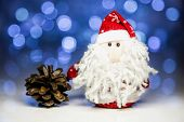 pic of pine cone  - Santa Claus or Father Frost and pine cone with Christmas lights at background on white surface - JPG